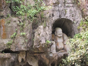 Laughing Buddha carving at the Buddhist temple and caves in Hangzhou